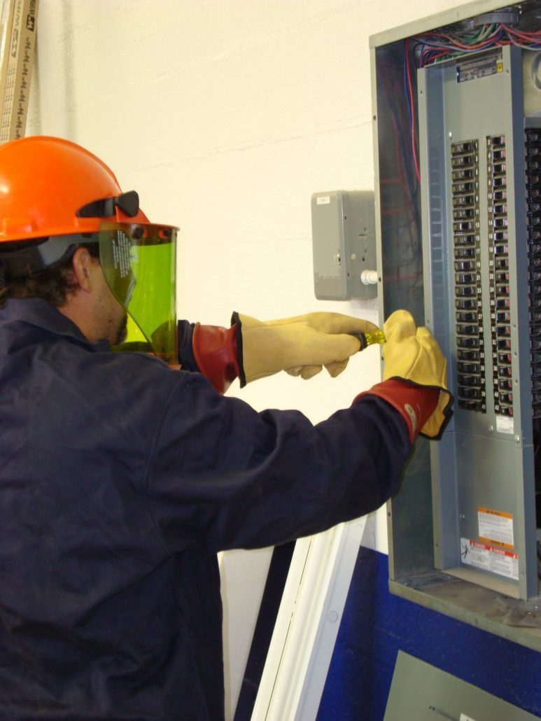 Electrician wearing safety gloves & shield doing preventative maintenance work on a panel with a screwdriver