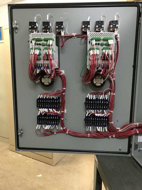 Photo of the backside of a control panel door which includes a lot of red connecting wires