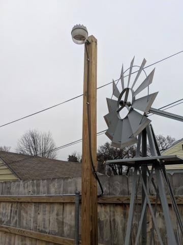 image outside of an outdoor residential light next to a house's backyard fence with a windmill garden decor