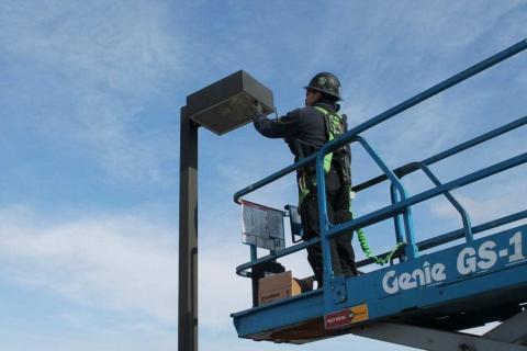 Decker Electric technician on a crane installing outdoor lighting at a high school sports field