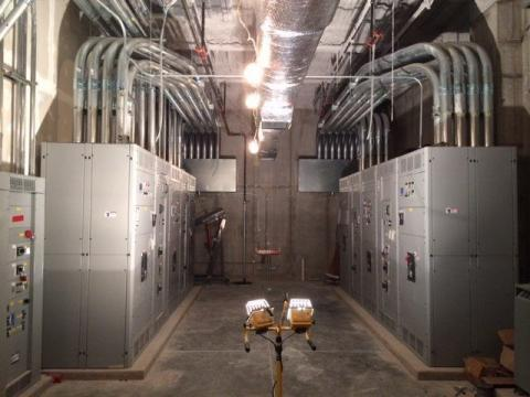 Image of the electrical room of a health care facility with many control panels and pipes