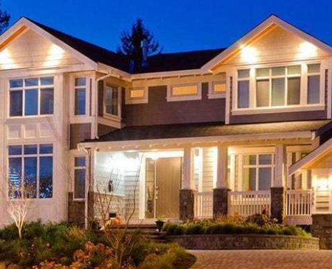 photo of a home's exterior that has many lights on its porch and around windows for security and beauty