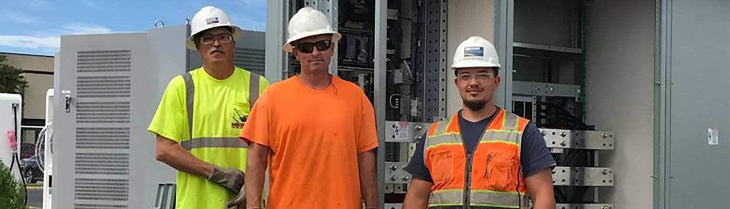 3 electricians in Decker Electric hard hats in front of electrical panel smiling