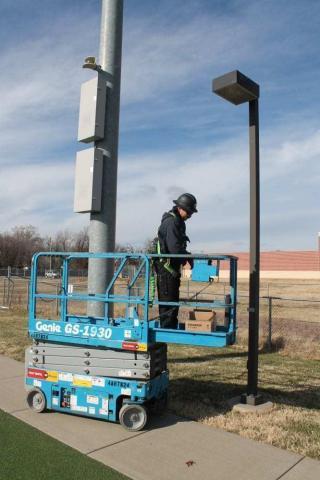 Decker Electric technician working on outdoor lighting at a high school
