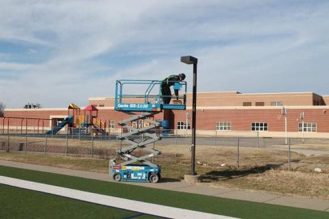 Decker Electric technician on a crane working on outdoor lighting at a high school sports field
