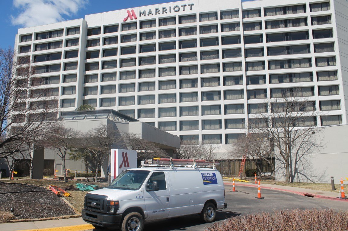 Photo of a Decker Electric van outside the large Marriott hotel as technicians handle electrical services
