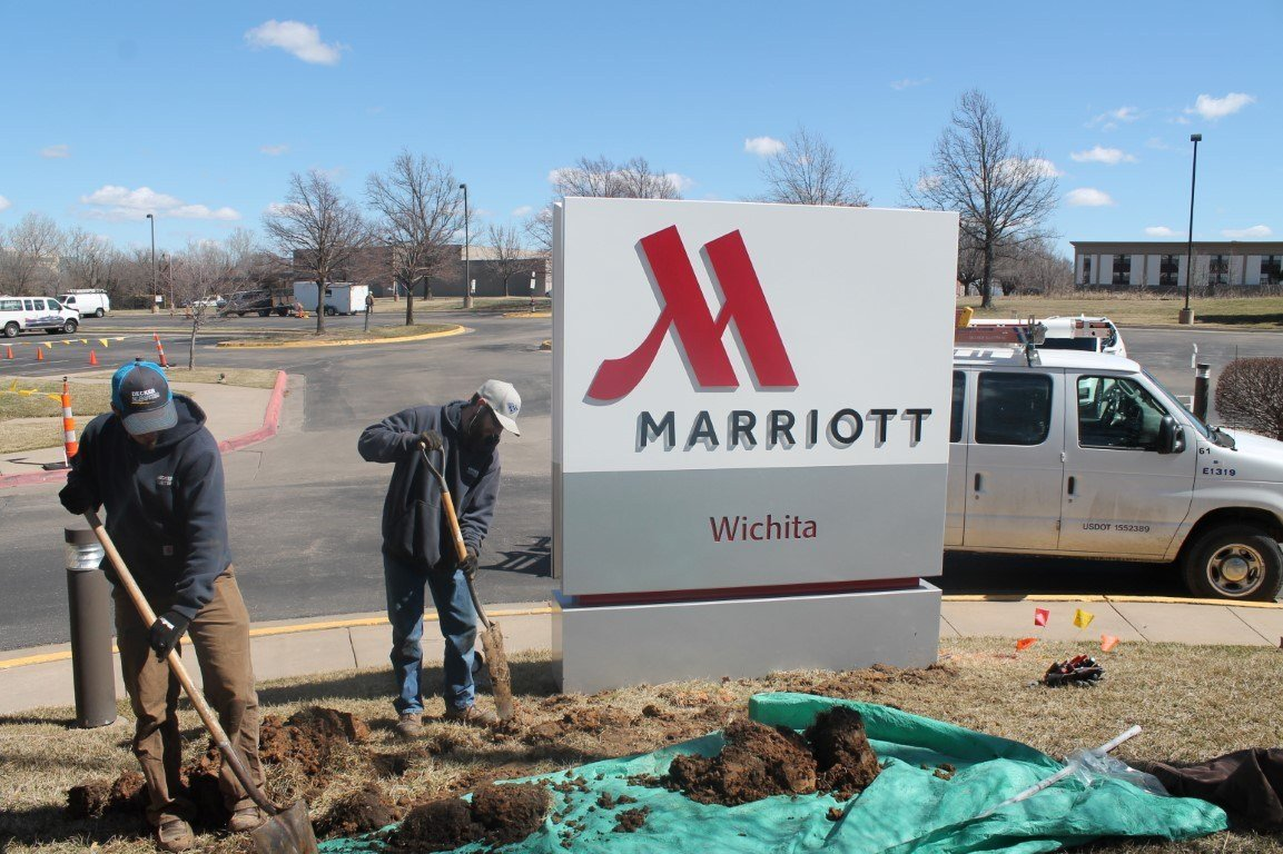 Decker Electric technicians digging holes next to a Marriott Hotel sign in Wichita to provide electrical services