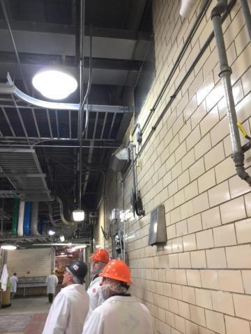 Large ceiling inside food service facility with workers in protective gear