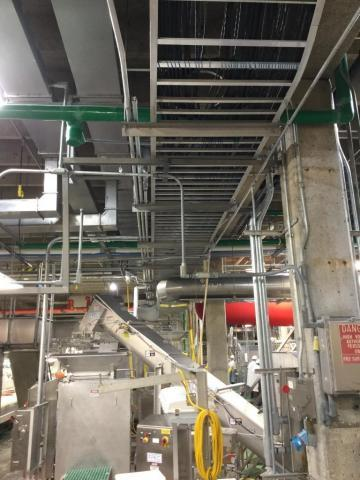 Inside a food service plant with a lot of mechanical structures and pipes