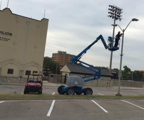 Decker Electric tech working in lift on sports lighting in parking lot